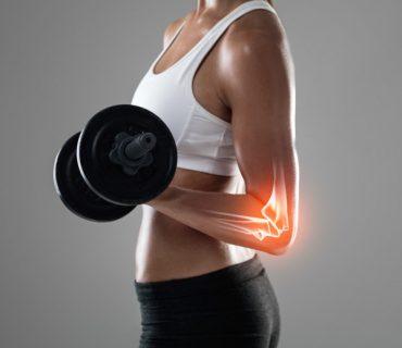 Ból łokcia u fitnesski podnoszącej hantlę na siłowni