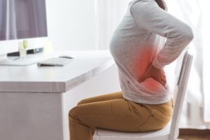 Ból pleców - pacjentka na krześle przy biurku