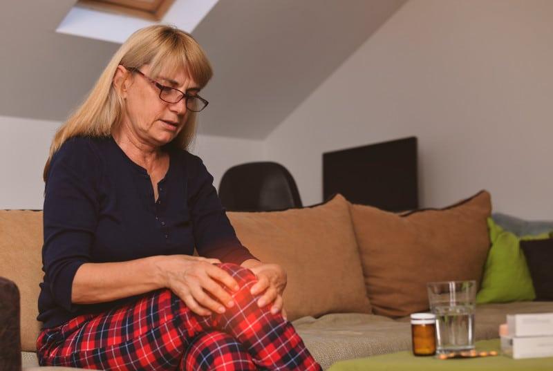 Kobieta siedząca na kanapie w domu z chondromalacją rzepki