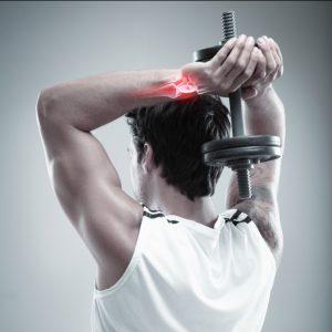 Uraz nadgarstka - ćwiczący mężczyzna z hantlem na siłowni