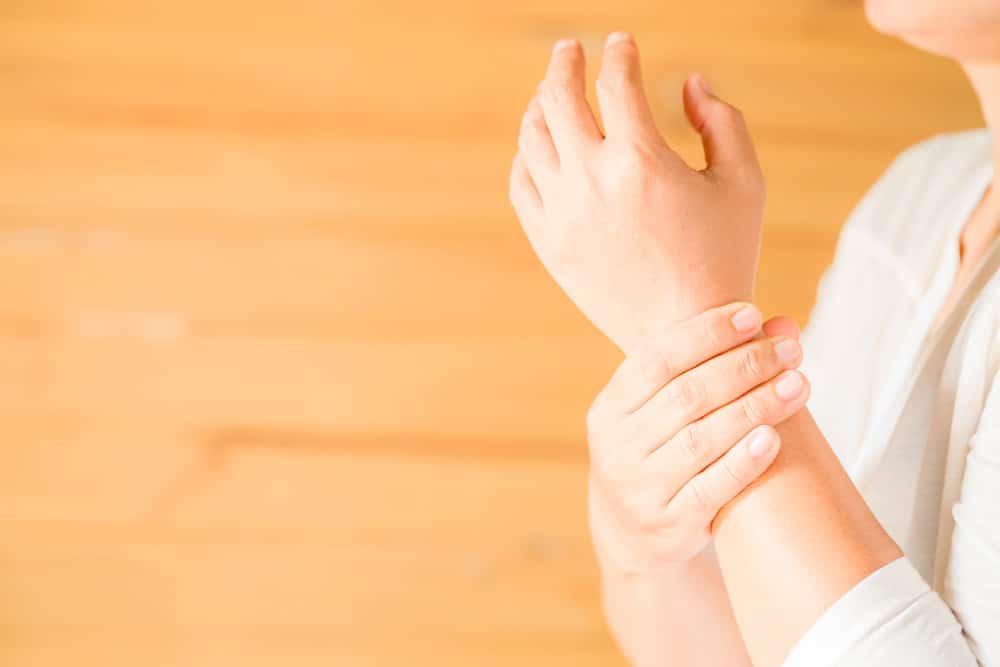 kobieta trzymająca się za nadgarstek - zespół cieśni