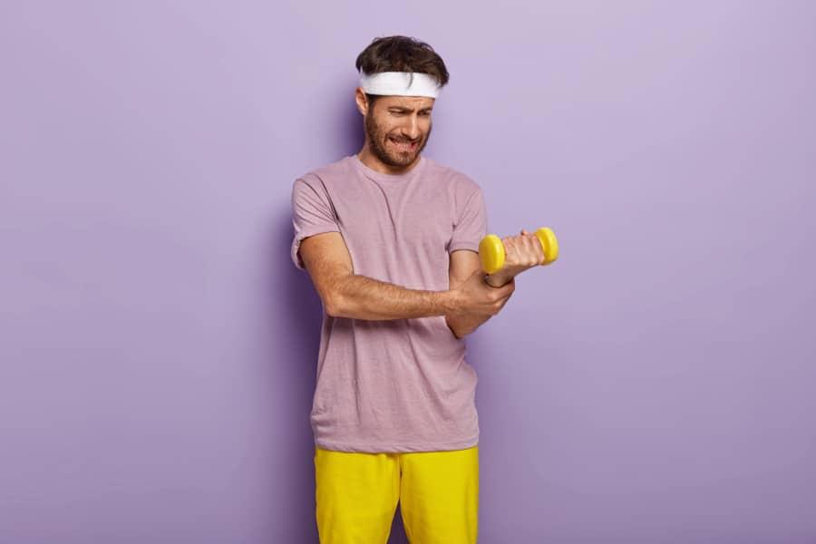 Zerwany biceps mężczyzny na siłowni