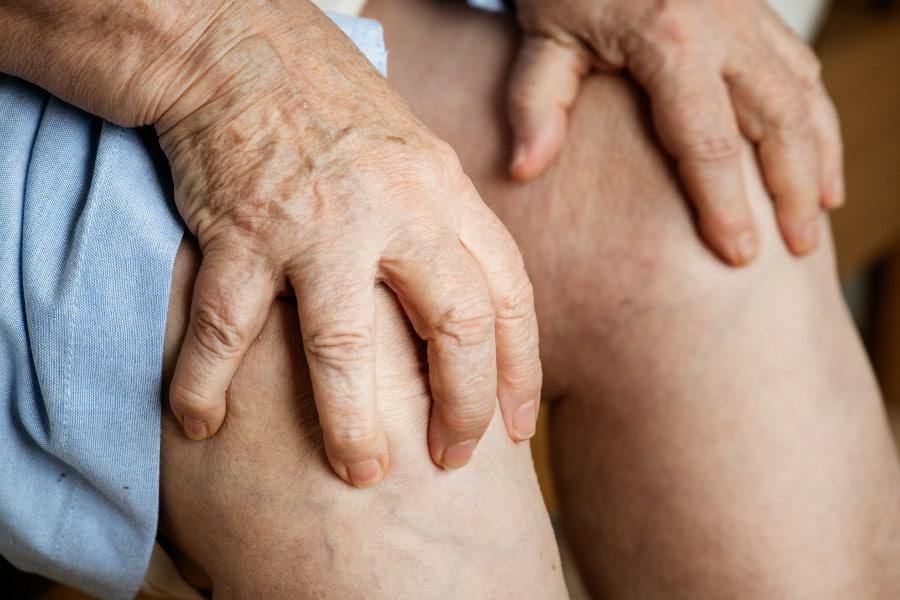 Zwyrodnienie stawu kolanowego u starszej kobiety trzymającej się za kolano z bólu