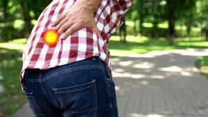 Mężczyzna zgięty w pół przez ból korzeniowy - w dolnej części kręgosłupa