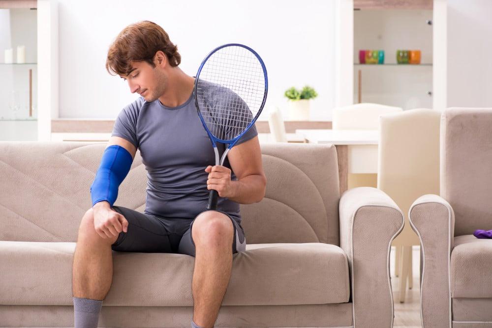Łokieć tenisisty - sportowiec z ortezą na łokciu i rakietą w dłoni